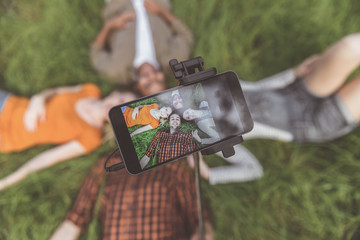 glad friends lying on the ground outdoors. Man holding selfie stick with smartphone and taking photo. Focus on device.Top view