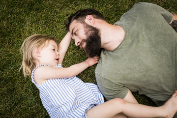 Father and daughter lying on grass in garden