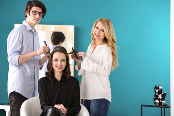 Professional hairdressers working with client in salon