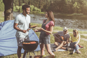 Satisfied youth relaxing beside the river. Man and woman standing near barbecue and conversing with pleasure. Couple sitting and playing the guitar on background