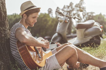 Side view of thoughtful guy playing guitar while sitting on grass and leaning on tree. Scooter on background