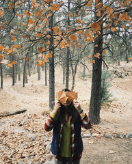 Woman holding autumn leaves while standing in forest