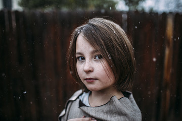 Portrait of confident girl at backyard during snowfall