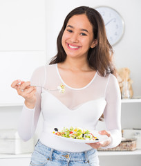 Smiling young girl eating tasty salad