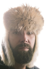 Close-up portrait of man wearing ushanka against clear sky