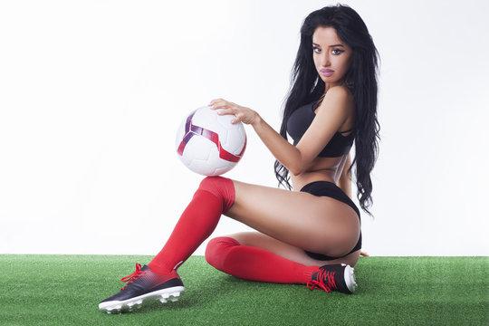 Beautiful fitness woman holding soccer ball.