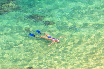Woman snorkeling over coral reef in Hanauma Bay Nature Preserve, Oahu, Hawaii, USA. Female lying above the crystalline water in tropical sea with american flag bikini. Watersport activity in Hawaii.