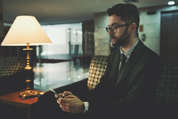 Portrait of a handsome bearded businessman in eyeglasses and a formal suit having work online chat via his smartphone while sitting on the couch in a lobby area of his office next to the lamp