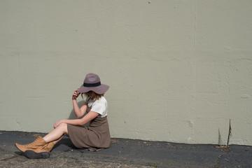 girl sitting covering her face full body