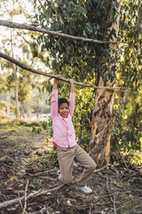 Happy boy hanging on branch in forest