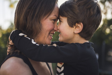 Close-up of happy mother and son looking at each other in yard