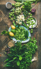 Spring healthy vegan food cooking ingredients. Flat-lay of vegetables, fruit, seeds, sprouts, flowers, greens over wooden background, top view, vertical composition. Diet, clean eating food concept