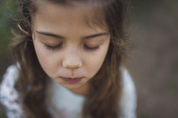 High angle close-up of girl with eyes closed standing outdoors