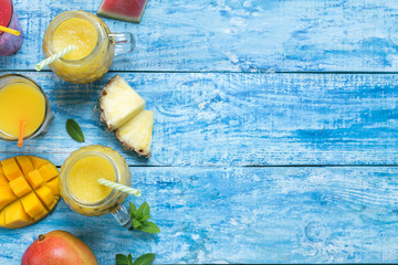 Fresh pineapple and mango smoothie in three glasses with straws with fruits on a blue wooden rustic background. copy space