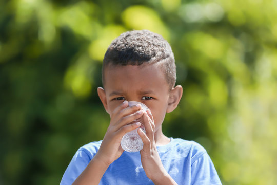 Cute African American boy drinking water from plastic cup, outdoors