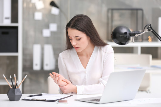 Young woman suffering from wrist pain in office