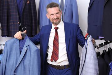 Handsome man choosing suit in shop