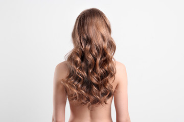 Naked young woman with long beautiful hair on white background