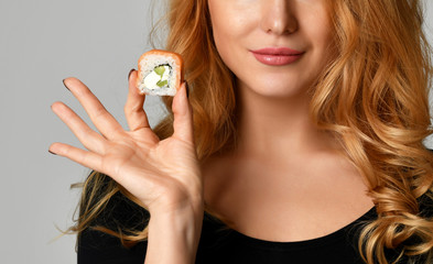 Woman with sushi girl hold sushi rolls in hands smiling on a light gray