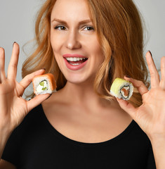 Woman with sushi woman eating hold sushi rolls in hands smiling