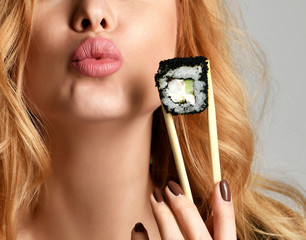 Woman with sushi hold philadelphia rolls in hands kissing on a light gray