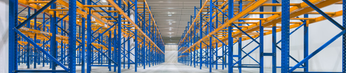 Wide image of empty shelves in logistics warehouse