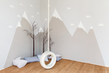 Playing room for a boy. Stylish kid room with illustration of mountains and bungee/swing. Mountains illustration in a child room