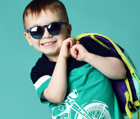 Preschool boy kid standing with backpack and sunglasses in shorts and t-shirt on green mint