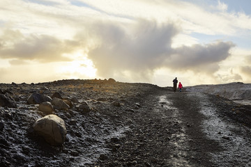 Rear view of father with daughter walking on mountain against cloudy sky