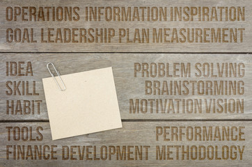 Business conceptual words. Wooden background with brown paper sheets or note.