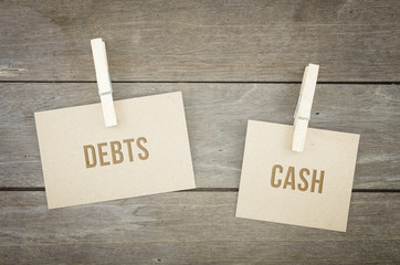 Debts or cash, business conceptual words, wooden background with brown paper sheets or note.