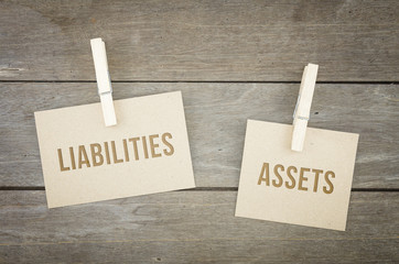 Liabilities or assets, business conceptual words, wooden background with brown paper sheets or note.