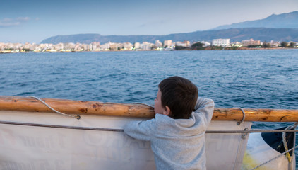 Boy looking at seascape and Chania city, Crete, Greece