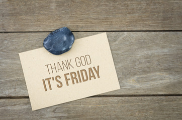 Thank god it is Friday, TGIF, lifestyle conceptual words, wooden background with brown paper sheets or note.