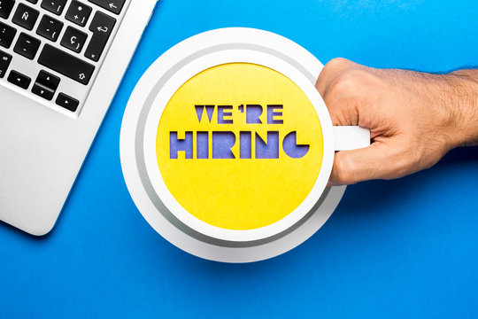 We are hiring phrase in cup of coffee paper concept on blue background