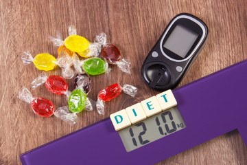 Electronic bathroom scale, glucometer with result of measurement and colorful candies, diabetes and reduction eating sweets concept