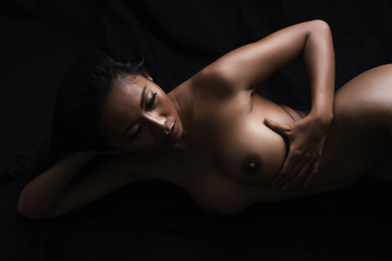 Low key artistic nude of sexy young Asian woman lying down on black cloth background