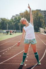 Female athlete does sport exercises in the stadium