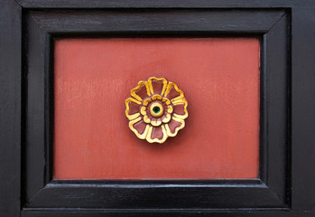 Black photo frame with gold and red wood flower decoration on wood wall background