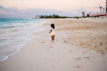 girl running on beautiful beach with turquoise water in Grace Bay during sunset, fully clothed, Providenciales, Turks and Caicos