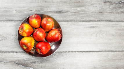 Table top view on seven red ripe apples in metal bowl placed on gray wood table.