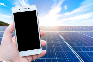 Men use cell phones blurred images in the solar panel background. As Renewable Energy and clean energy.