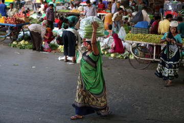 A woman carries a bag of vegetables on her head as she crosses a road at a wholesale market in Ahmedabad