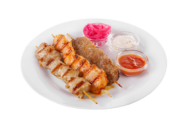 Shish kebab, beef, lamb, pork, chicken meat on the grill, barbecue, without garnish on a plate, isolated on white background. Marinated onion, mayonnaise, tar tar, ketchup, tomato sauce Side view