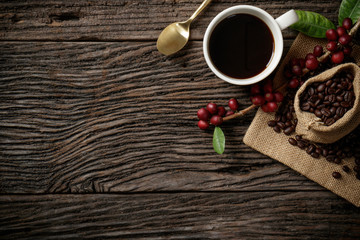 Top view mockup on wood background with a cup of coffee and red ripe coffee beans. Free space for your text.