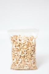 Cashew nuts in plastic bag packaging on white background.