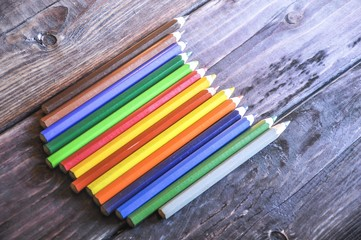 Colorful pencils on a wood background