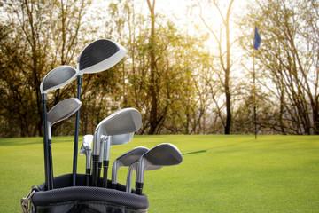 Golf equipment on green field background.