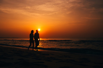 silhouettes of a couple in love on the beach by the sea on the background of orange sunrise in summer