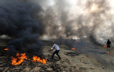 Palestinian protester moves burning tires during clashes with Israeli troops at Israel-Gaza border, in the southern Gaza Strip